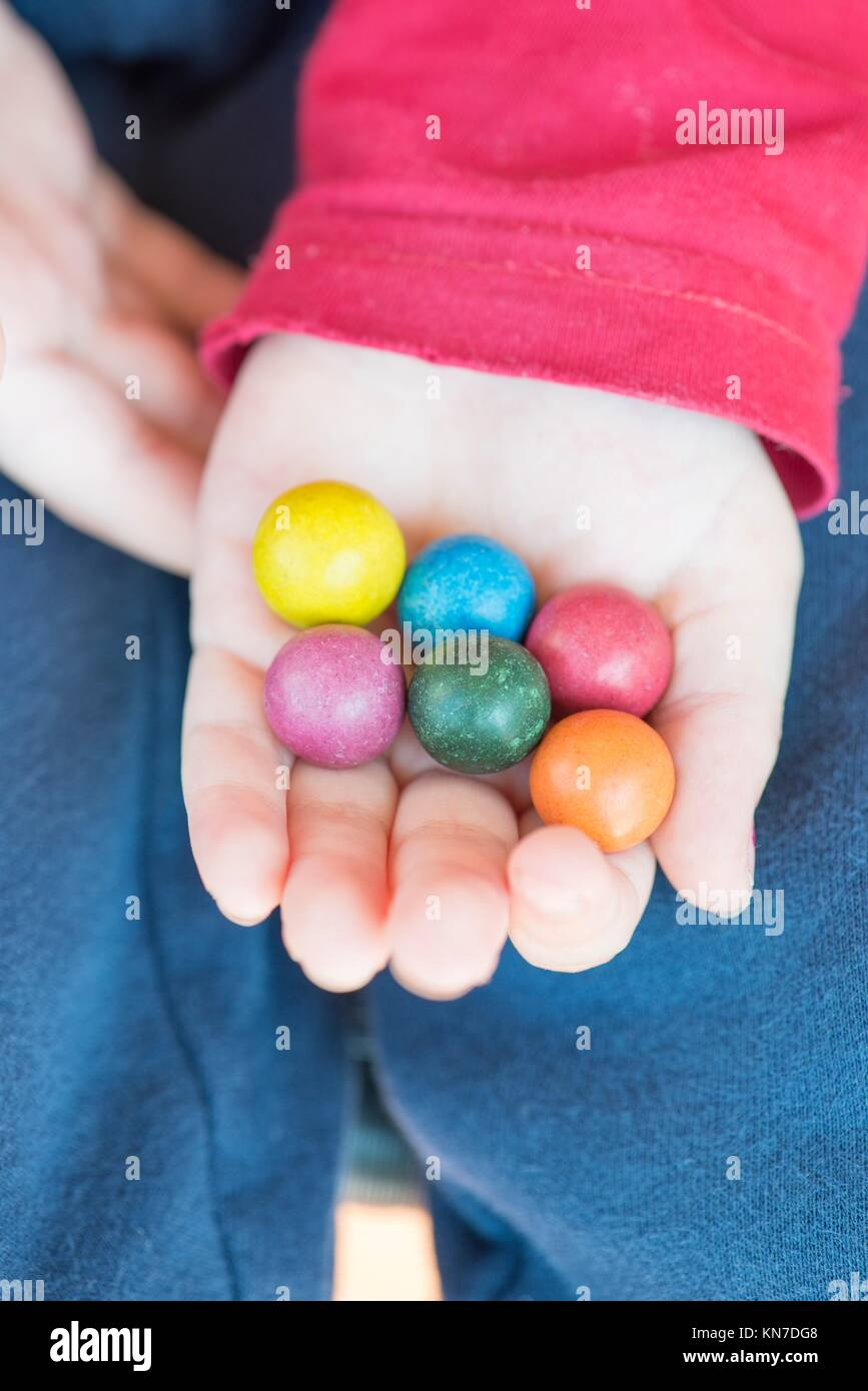 Childhood moment. Hand of child holding colorful toy marbles. - Stock Image
