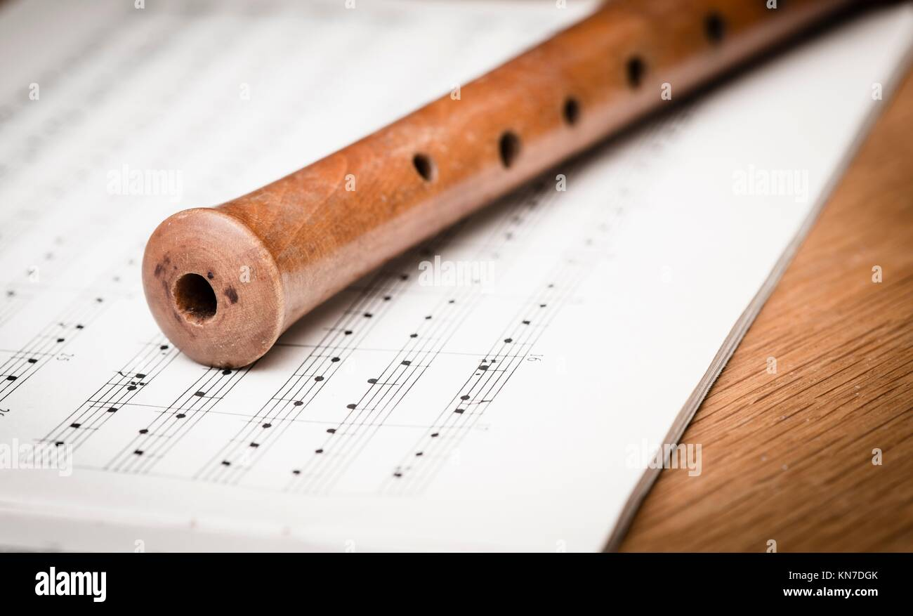 Close up of wooden recorder and notes on paper. Concept of playing the flute, music and melody. - Stock Image