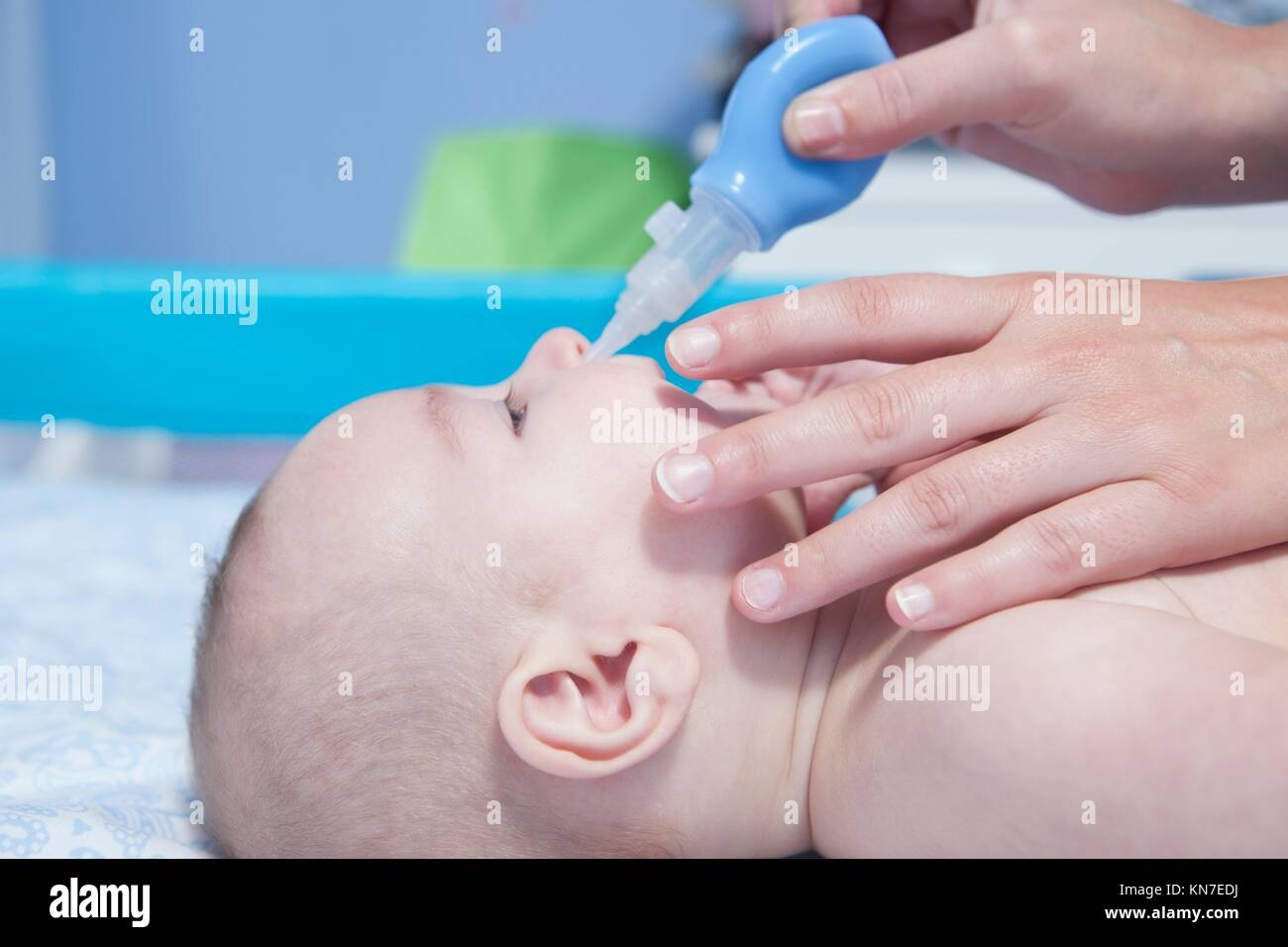 Mother using baby nasal aspirator. She is doing a mucus suction to three months baby boy. Stock Photo