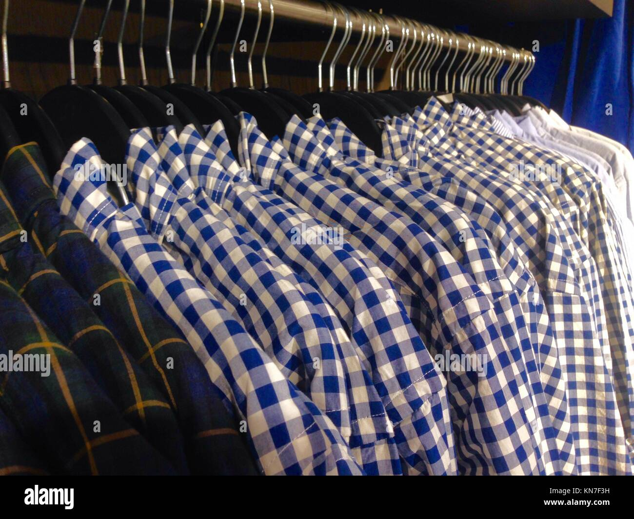 Hanger full of men's chequered shirts at shop. - Stock Image