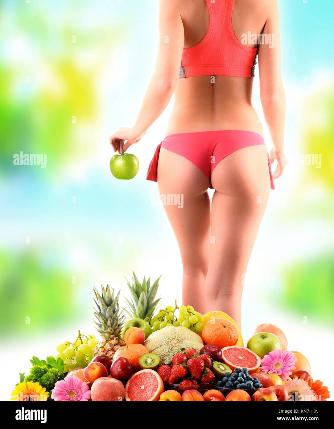 Weight loss. Slim woman holding an apple and composition with variety of fresh fruits. - Stock Image