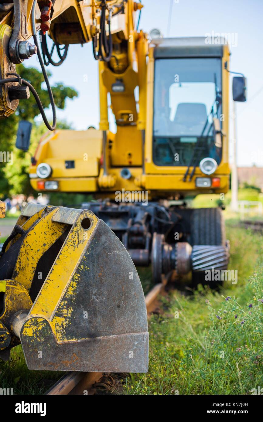 Railway construction equipment including hyralic shovel on rails. - Stock Image