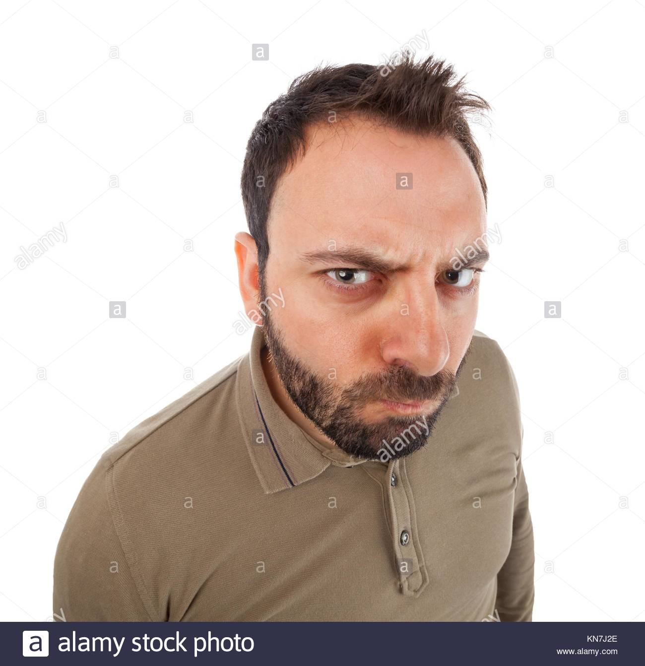 Young man with angry expression on white background. - Stock Image