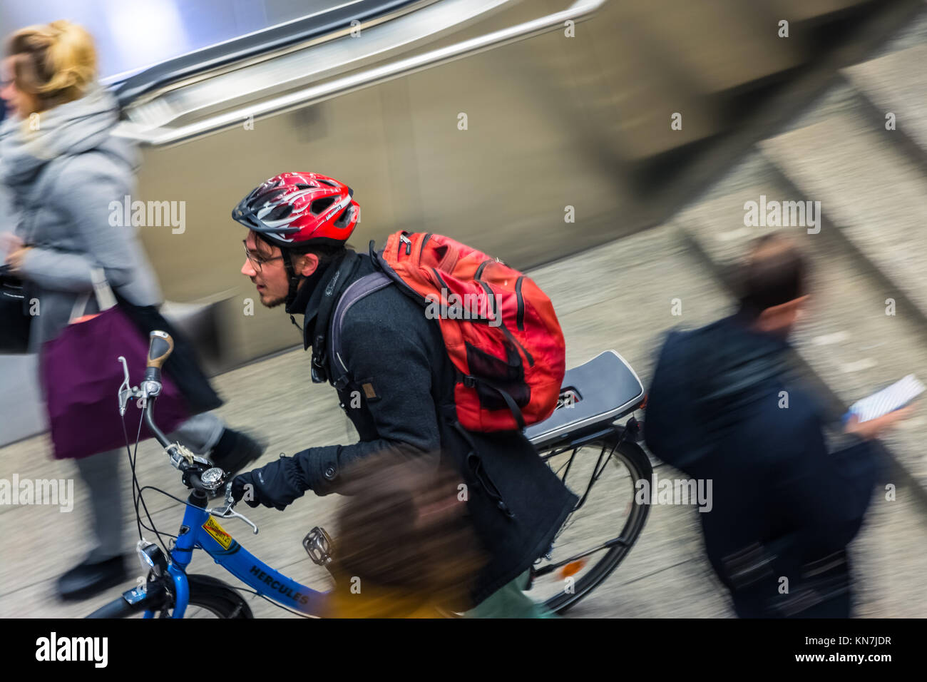 Man Rushing to Train with Bike in German Train Station Public Transportation Etiquette Blurring - Stock Image
