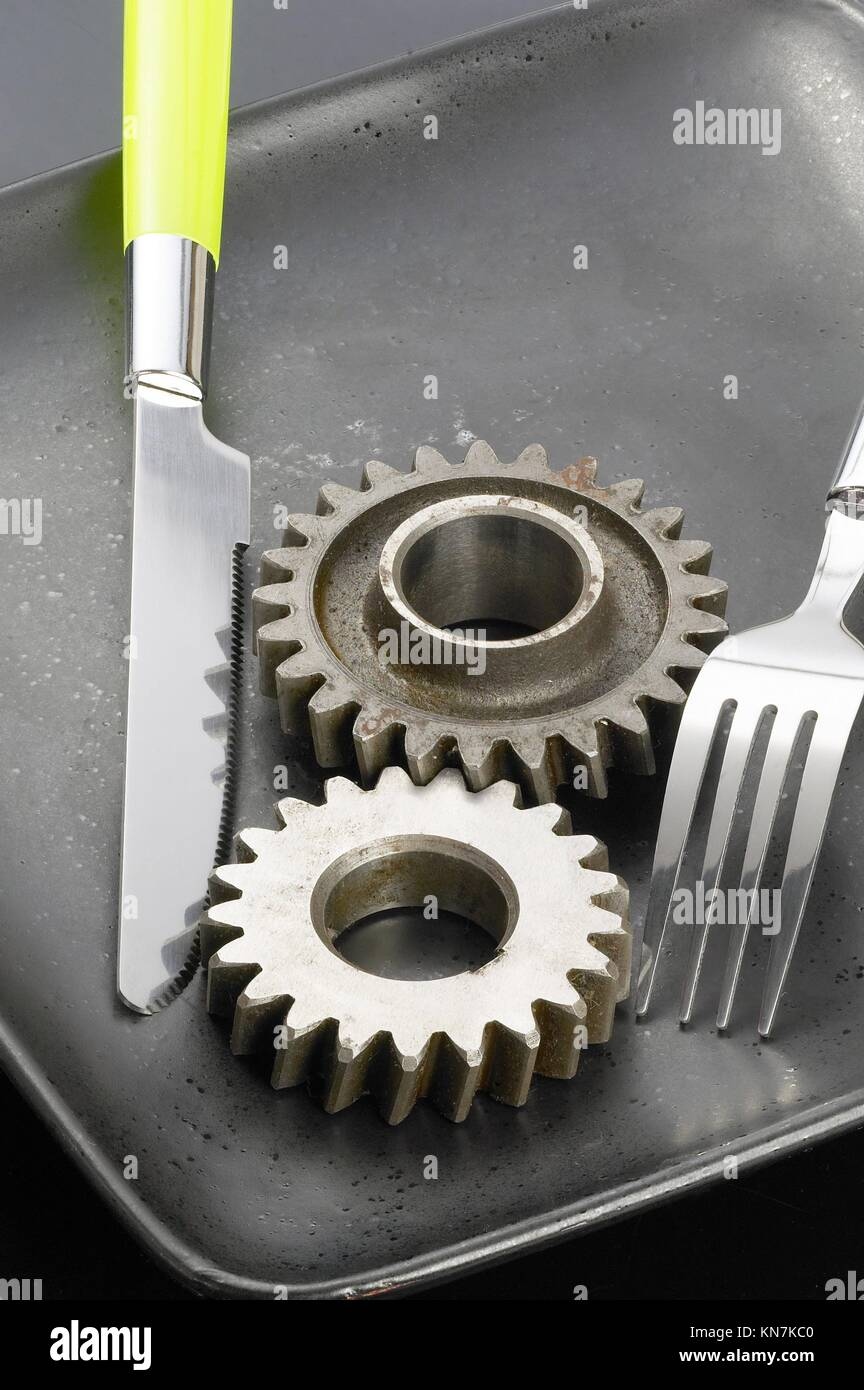 gearwheels on a black plate with knife and fork. - Stock Image