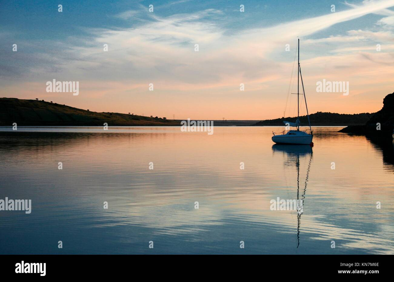 Sailboat anchored in the middle of Alange Reservoir, Spain. Sunset hour. - Stock Image