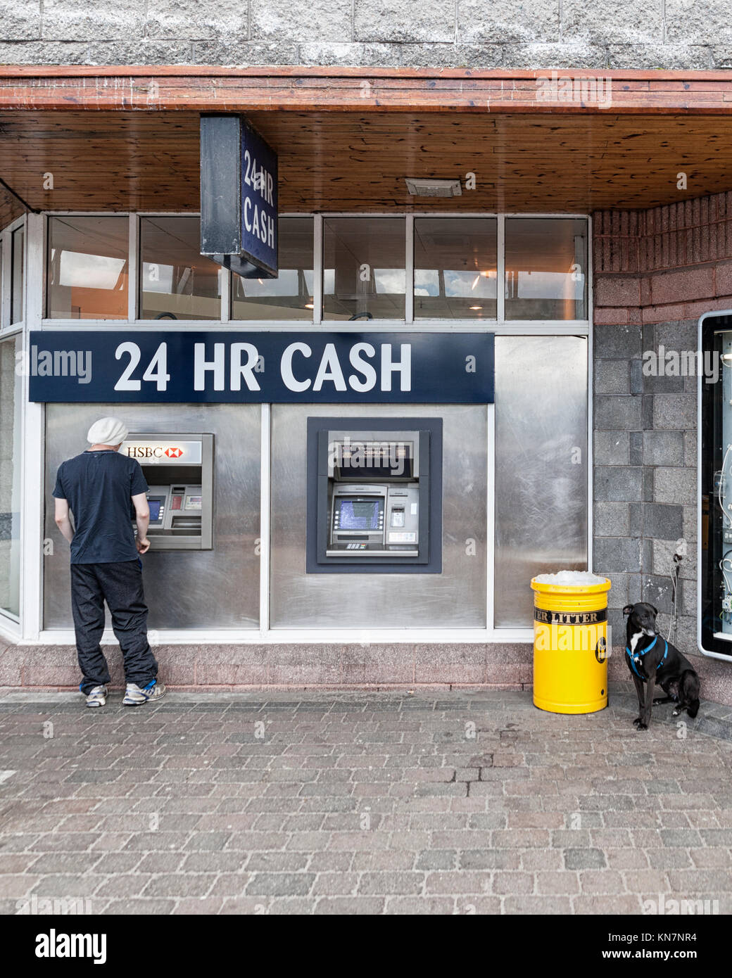 Young adult man withdrawing cash from 24 hour cash point ATM and tied up dog waiting close by, Scotland, UK  Model Stock Photo