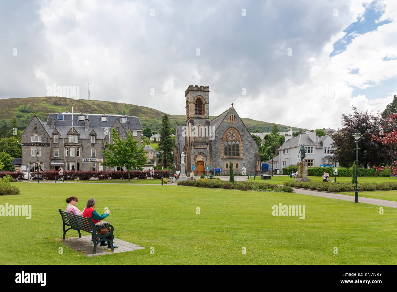 Two ladies sitting on park bench at the Parade in Fort William, Scotland, UK  Model Release: No.  Property Release: Stock Photo