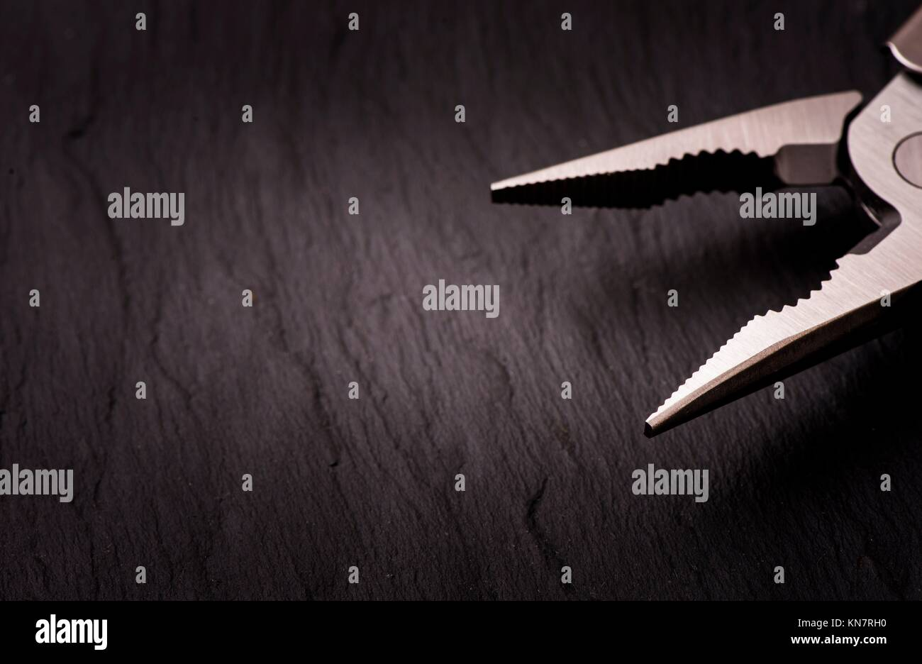 Black stone background and steel pliers. Backdrop for work tools, diy and home improvement. - Stock Image