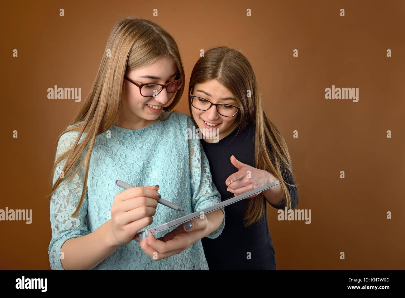 Two teen young friends using a computer tablet. - Stock Image