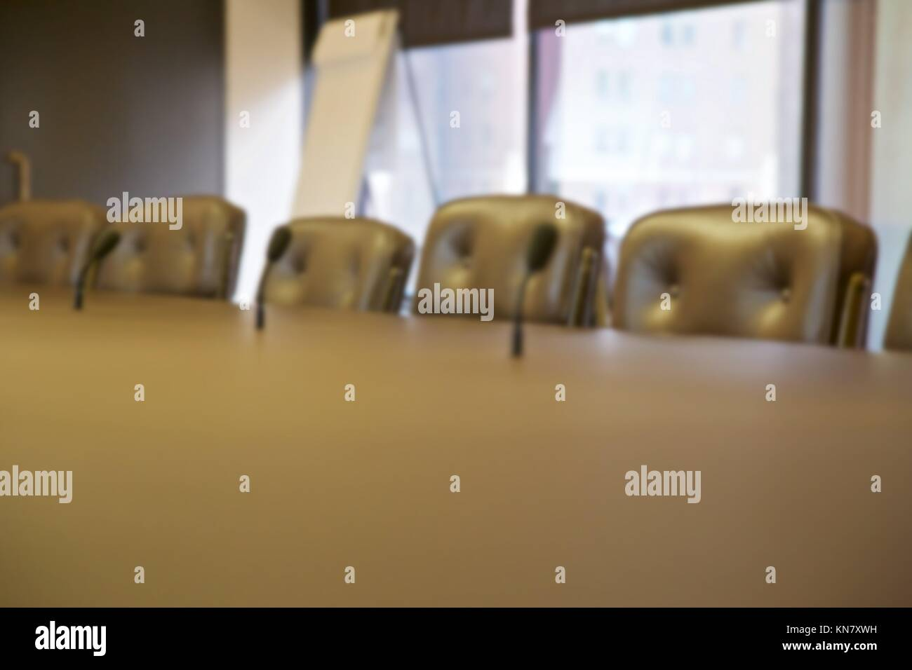 Background blur of empty seats at a board room table. - Stock Image