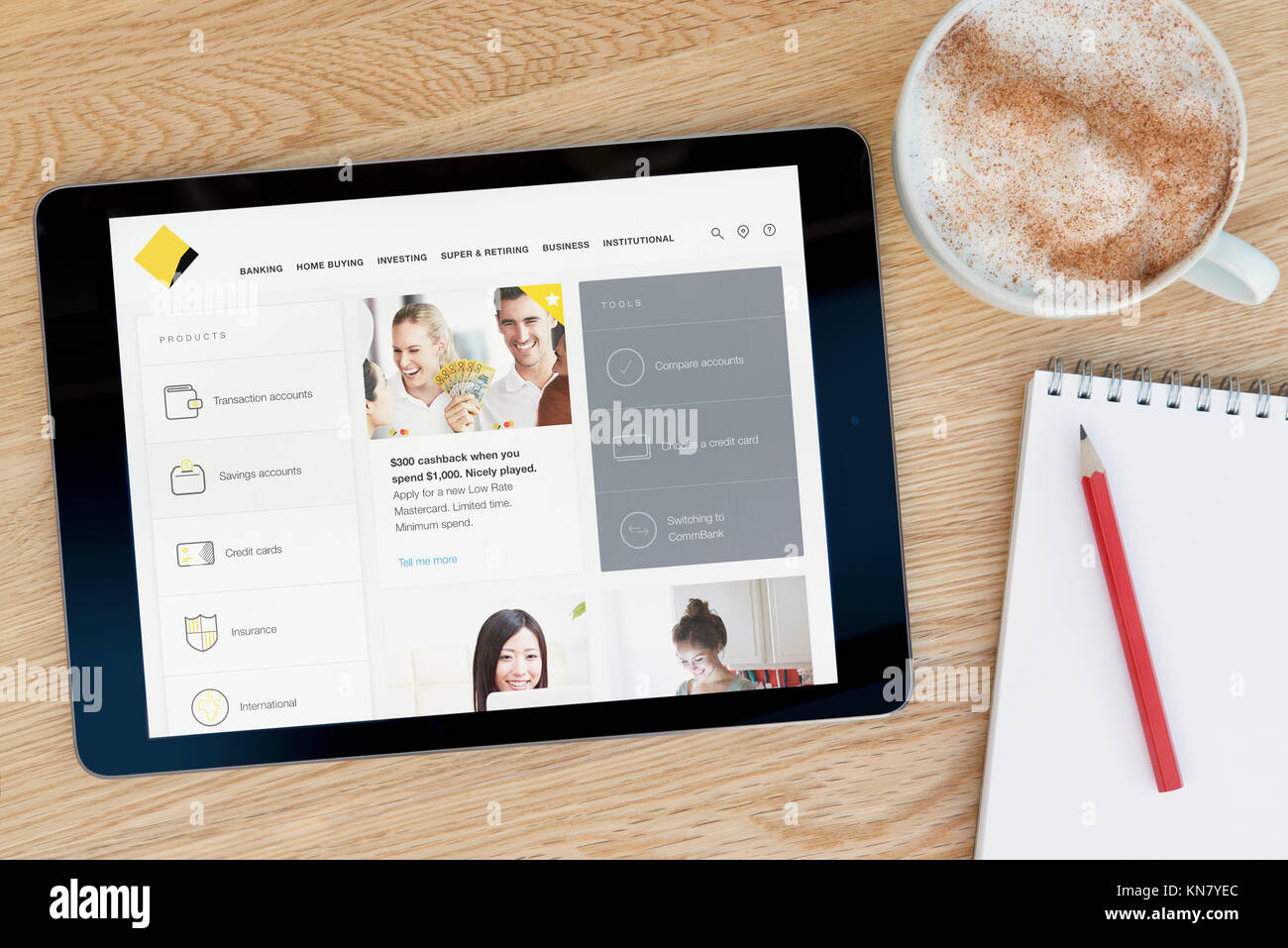 The Commonwealth Bank website on an iPad tablet device which rests on a wooden table beside a notepad and pencil - Stock Image