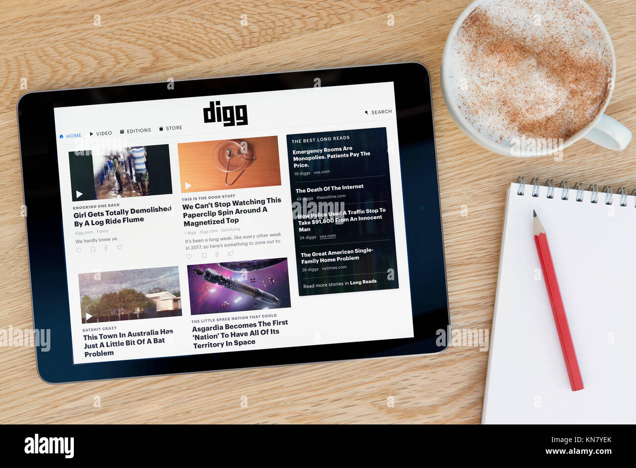 The Digg website on an iPad tablet device which rests on a wooden table beside a notepad and pencil and a cup of - Stock Image