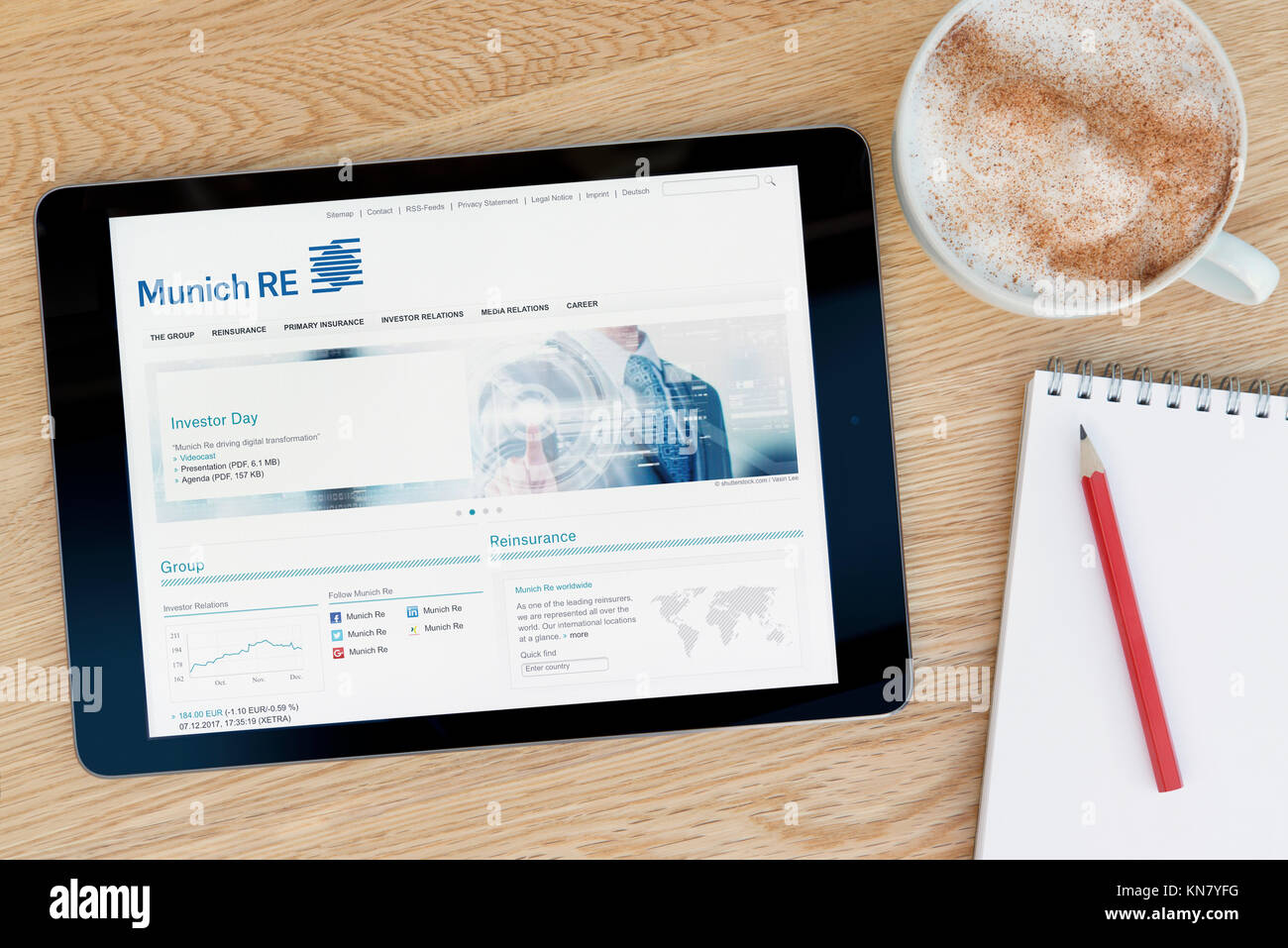 The Munich RE website on an iPad tablet device which rests on a wooden table beside a notepad and pencil and a cup - Stock Image