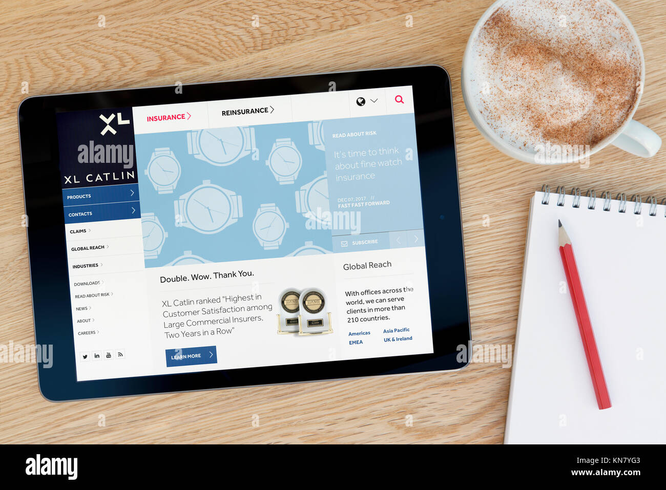 The XL Catlin website on an iPad tablet device which rests on a wooden table beside a notepad and pencil and a cup - Stock Image