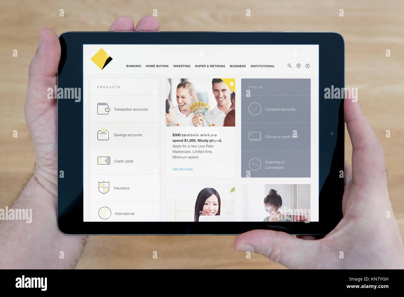 A man looks at the Commonwealth Bank website on his iPad tablet device, shot against a wooden table top background - Stock Image