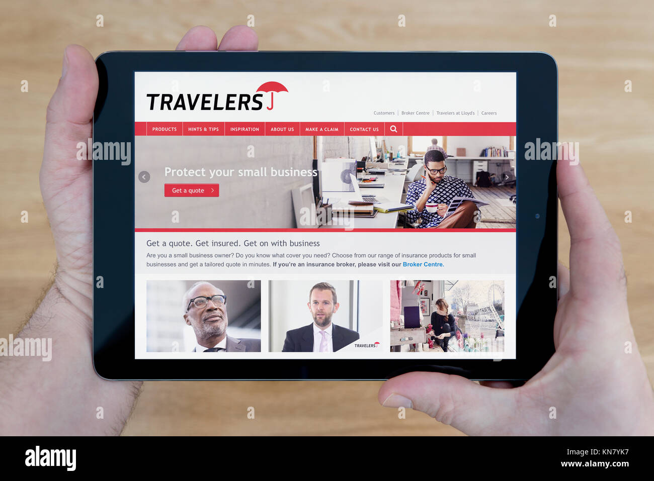 A man looks at the Travelers website on his iPad tablet device, shot against a wooden table top background (Editorial - Stock Image