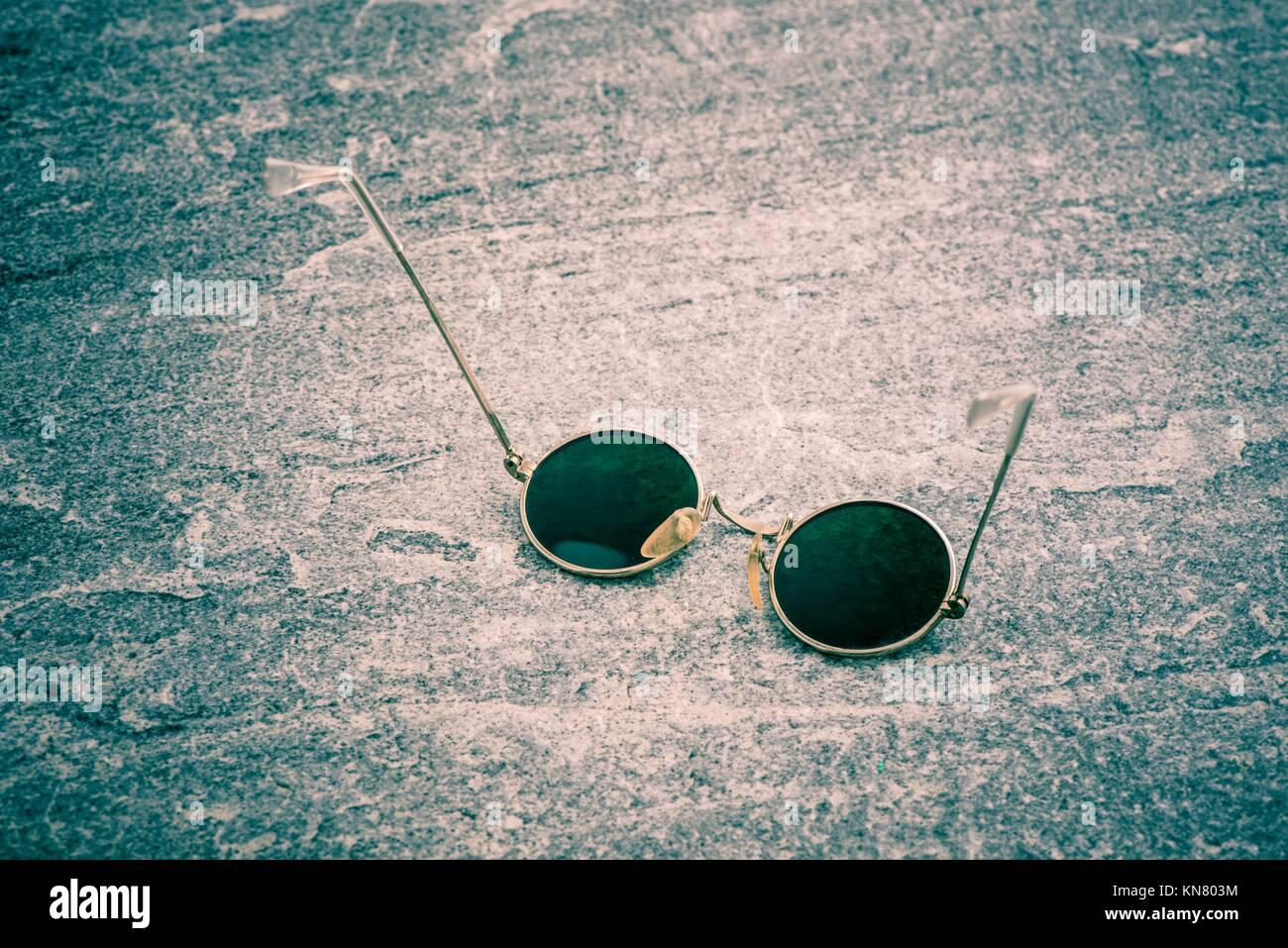 Round sunglasses on stone table, Retro eyewear. Still life of cool design accessory. - Stock Image
