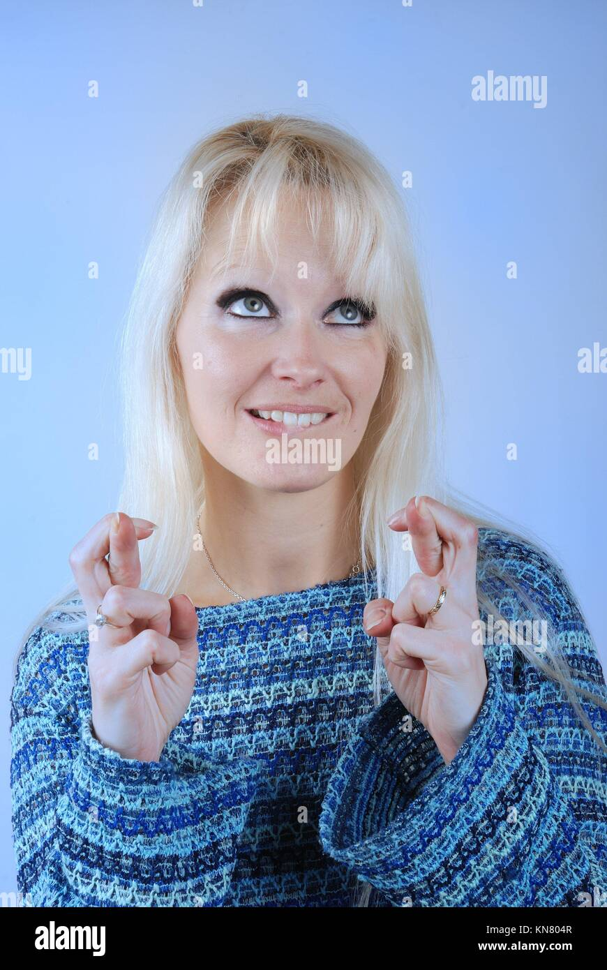 Young blond woman fingers crossed. - Stock Image