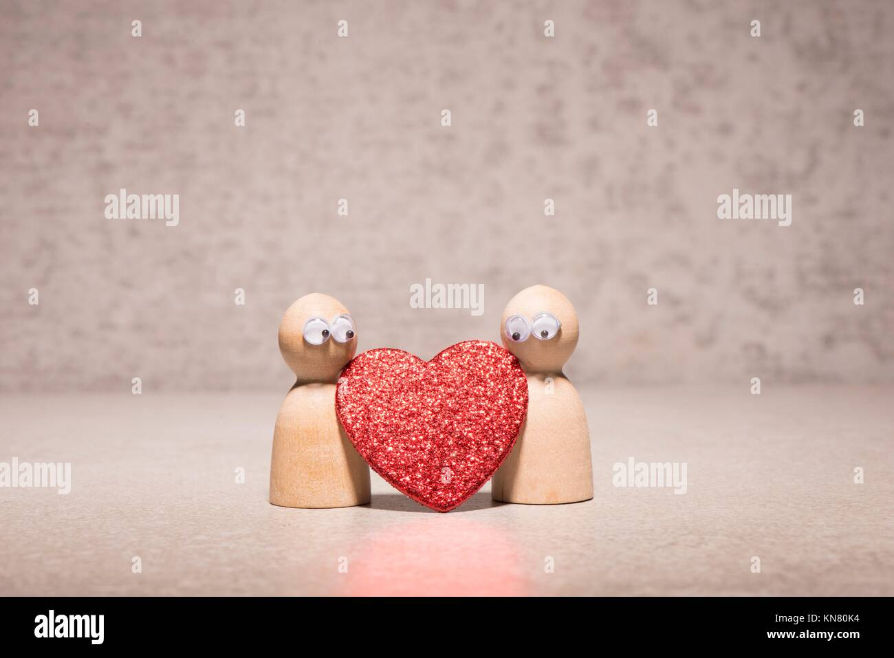 Couple holding red heart. Wooden figures with cute and funny symbol of love. Concept of romantic feelings, dating - Stock Image