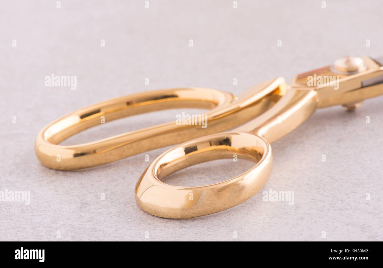 Gold colored scissors on a stone table. Equipment used for sewing or tailoring work. - Stock Image