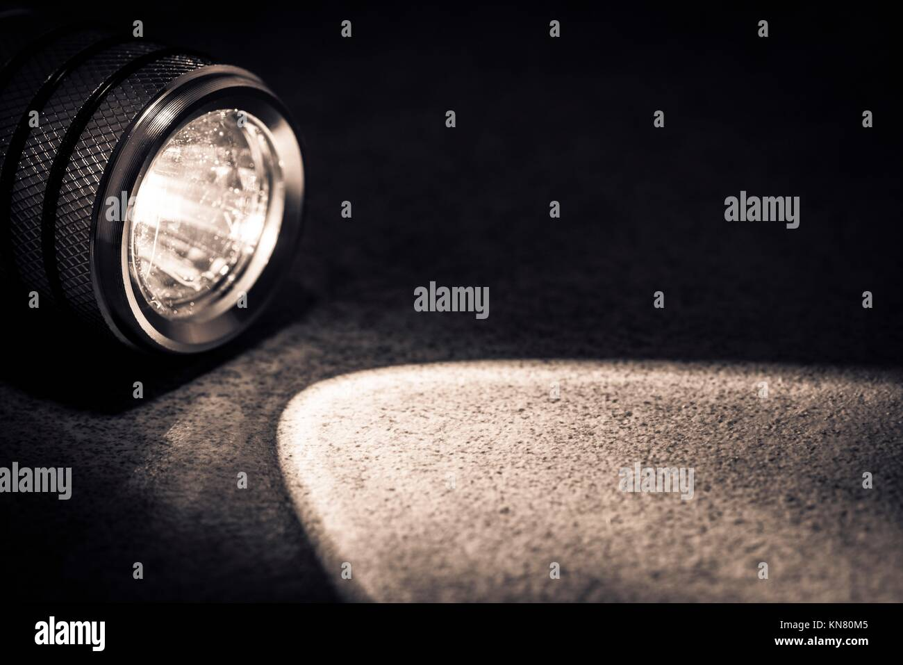 Flashlight and a beam of light in darkness. A modern led light with bright projection on dark stone. Surface with - Stock Image