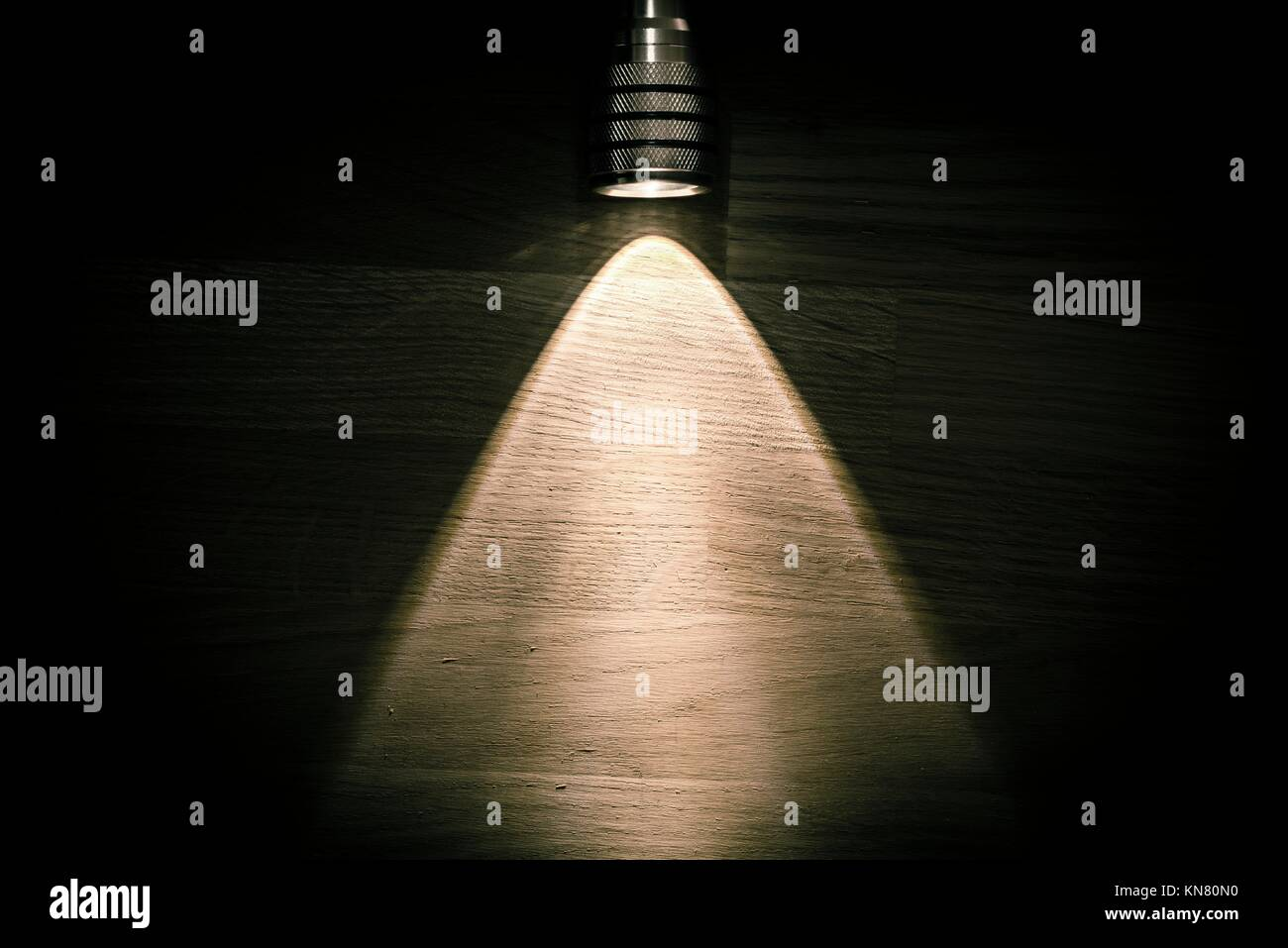 Flashlight and a beam of light in darkness. A modern led light with bright projection on dark wood table. Surface - Stock Image