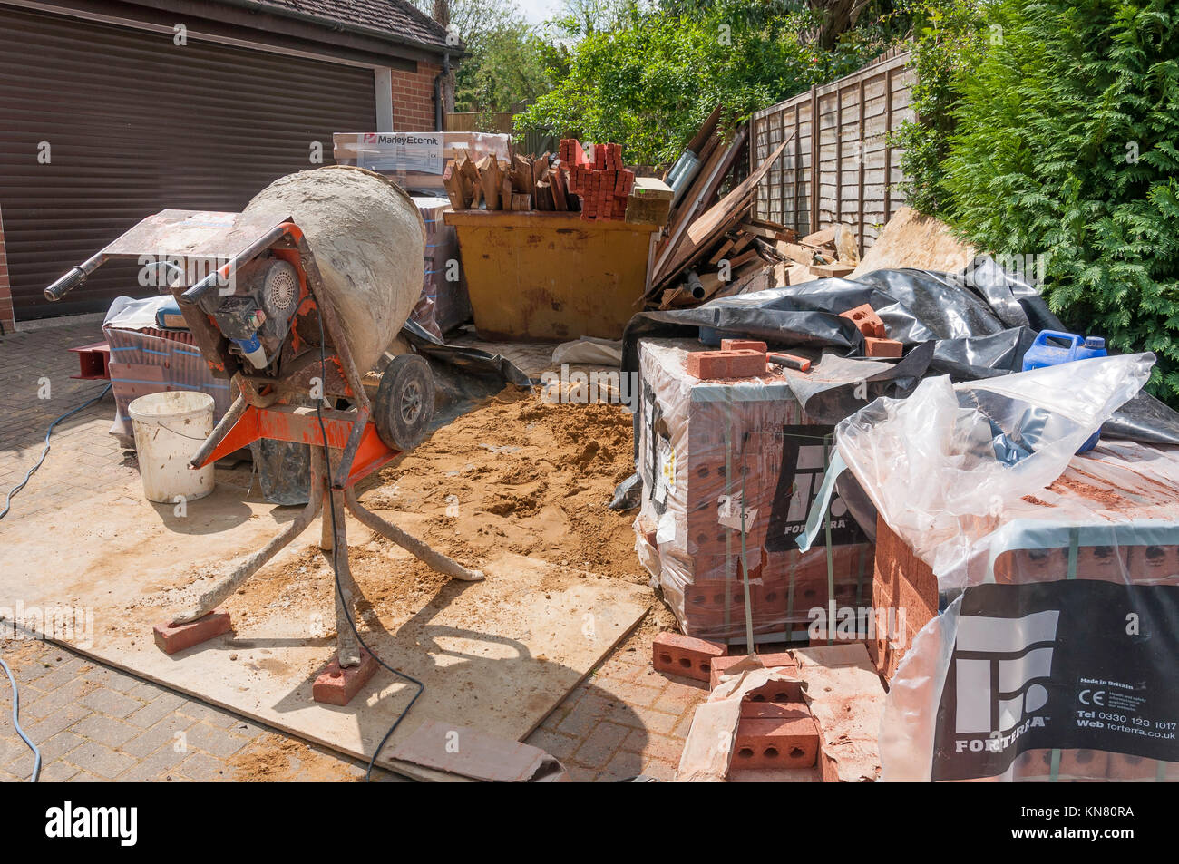Builder's work station with concrete mixer, sand, bricks and timber, Hungerford, Berkshire, England, United - Stock Image