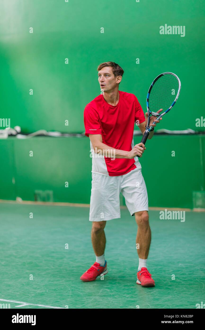 Professional tennis player have a training at indoor court. Stock Photo