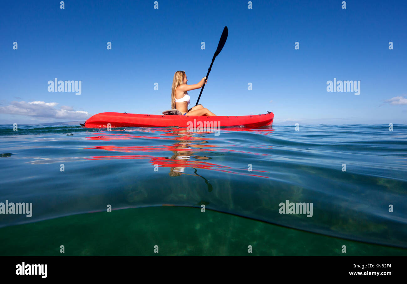 Healthy female  paddles a red kayak at Makena, Maui, Hawaii. Split level view. - Stock Image