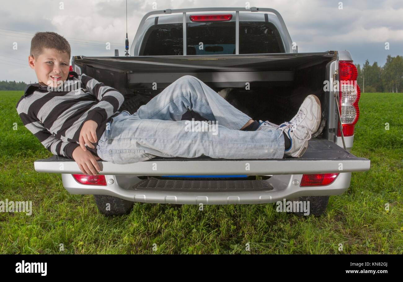 boy laying on car trunk on natural background. - Stock Image