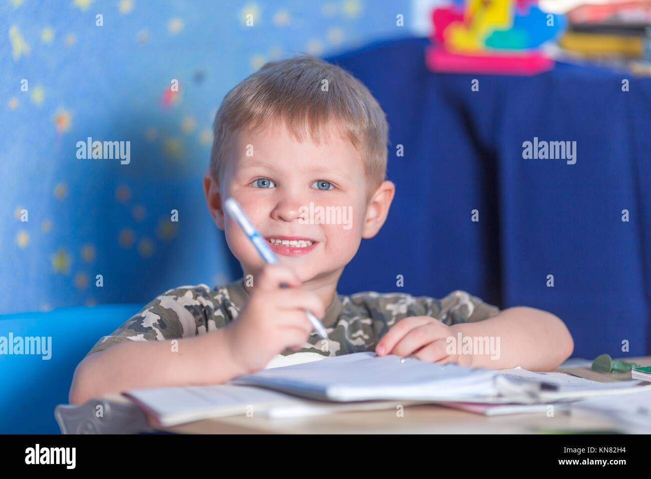 Preschool smiling boy learning to write literacy. - Stock Image