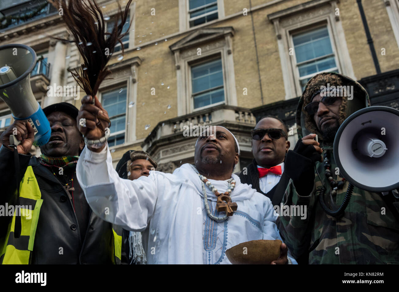 December 9, 2017 - London, UK. 9th December 2017. A man in white robes ends an African libation ceremony in honour - Stock Image