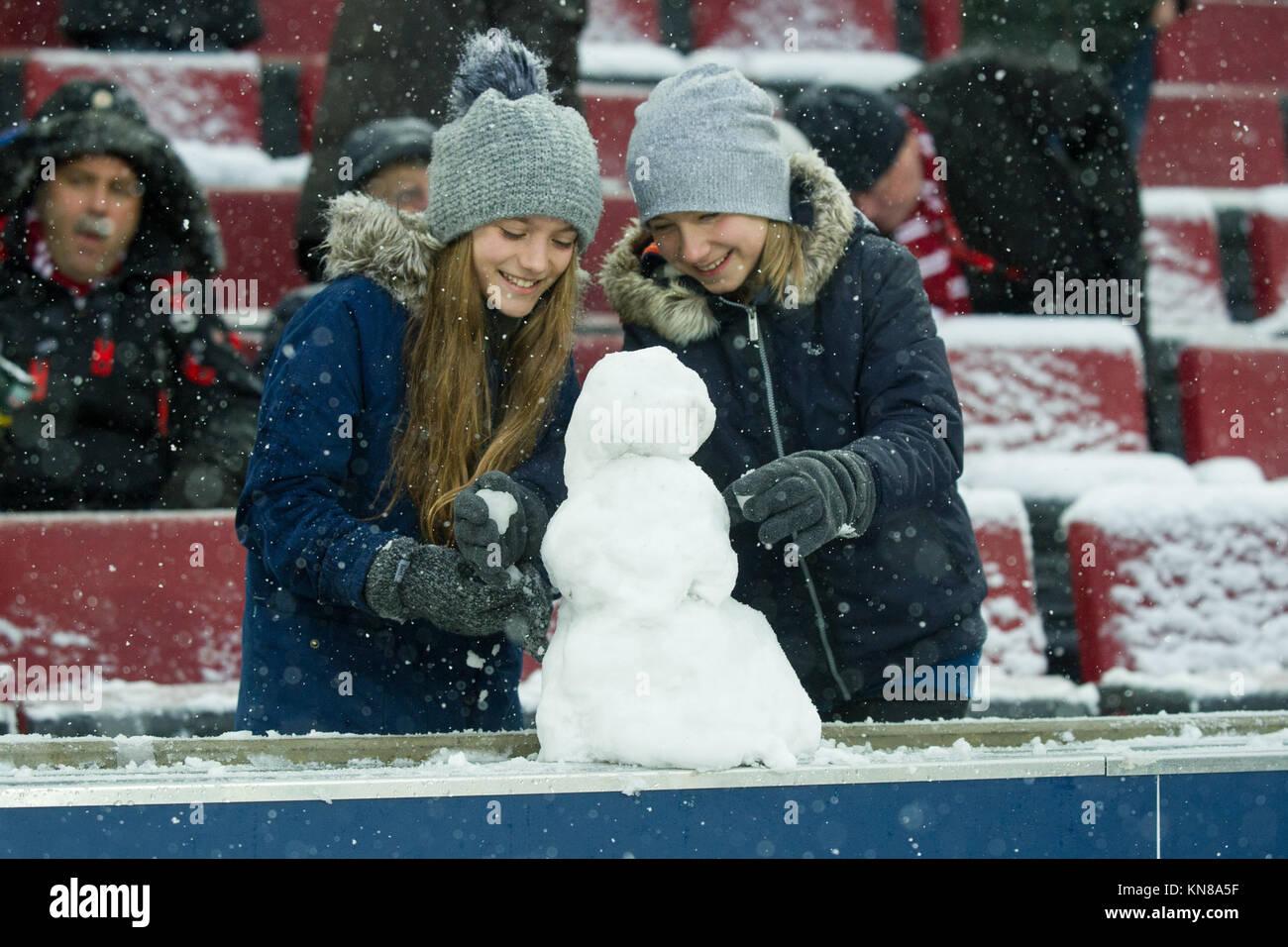 Koeln, Deutschland. 10th Dec, 2017. Zwei Maedchen bauen auf der Tribiuene einen Schneemann, Trib ne, Spielverspaetung, Stock Photo