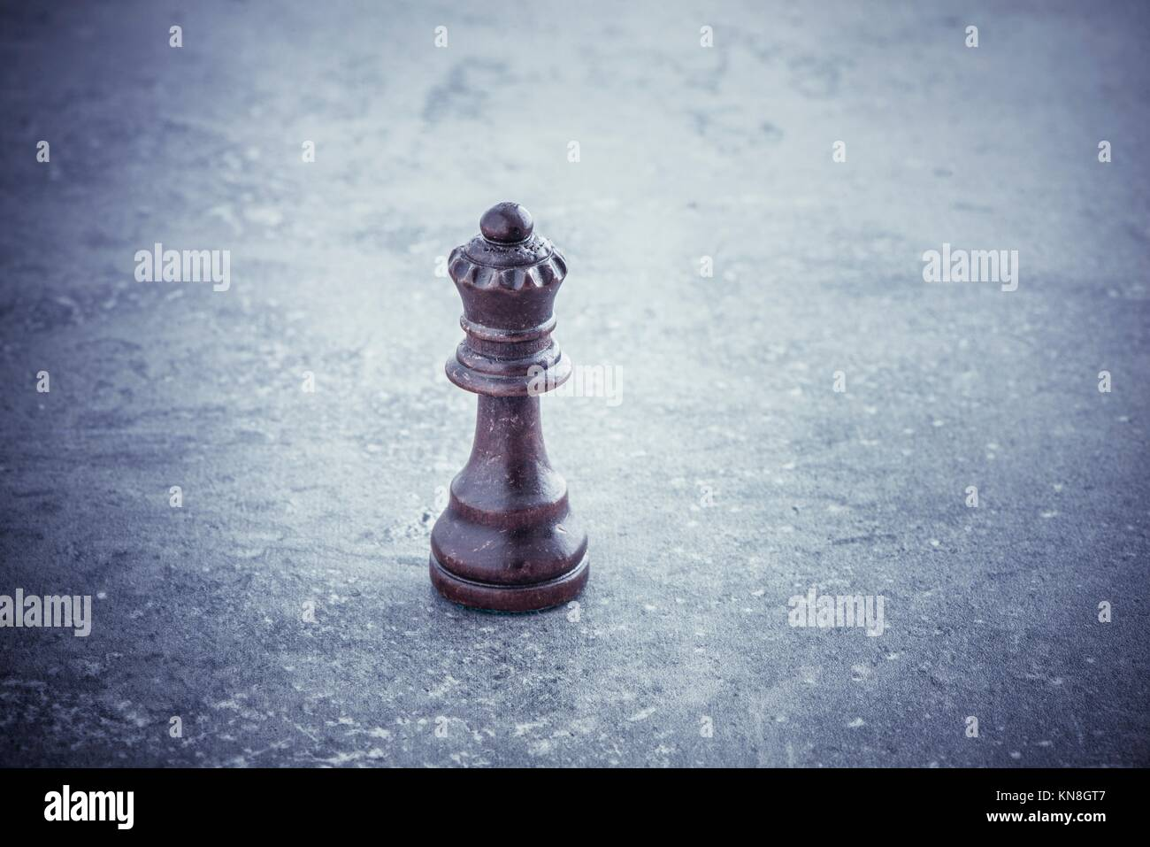 One black chess queen standing alone on stone table with copy space. Concept of strategy, competition and leadership. - Stock Image