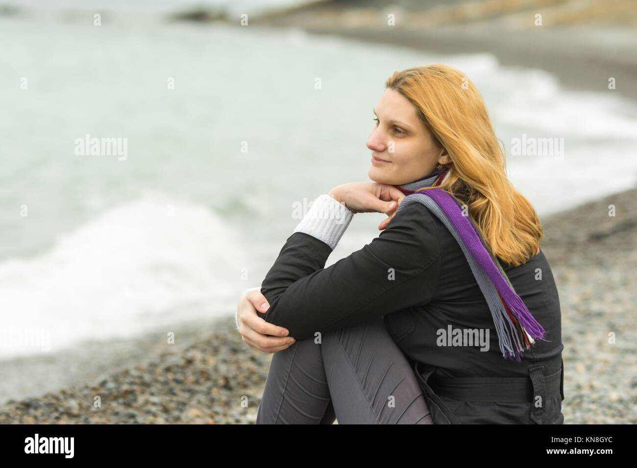 A girl sits on a pebble beach by the sea on a cloudy day in cold weather, and smiles enigmatically. Stock Photo