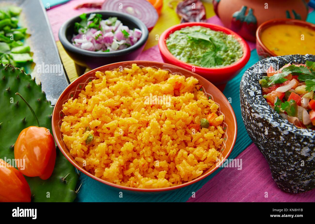 Mexican yellow rice with chilis and sauces in colorful background. Stock Photo