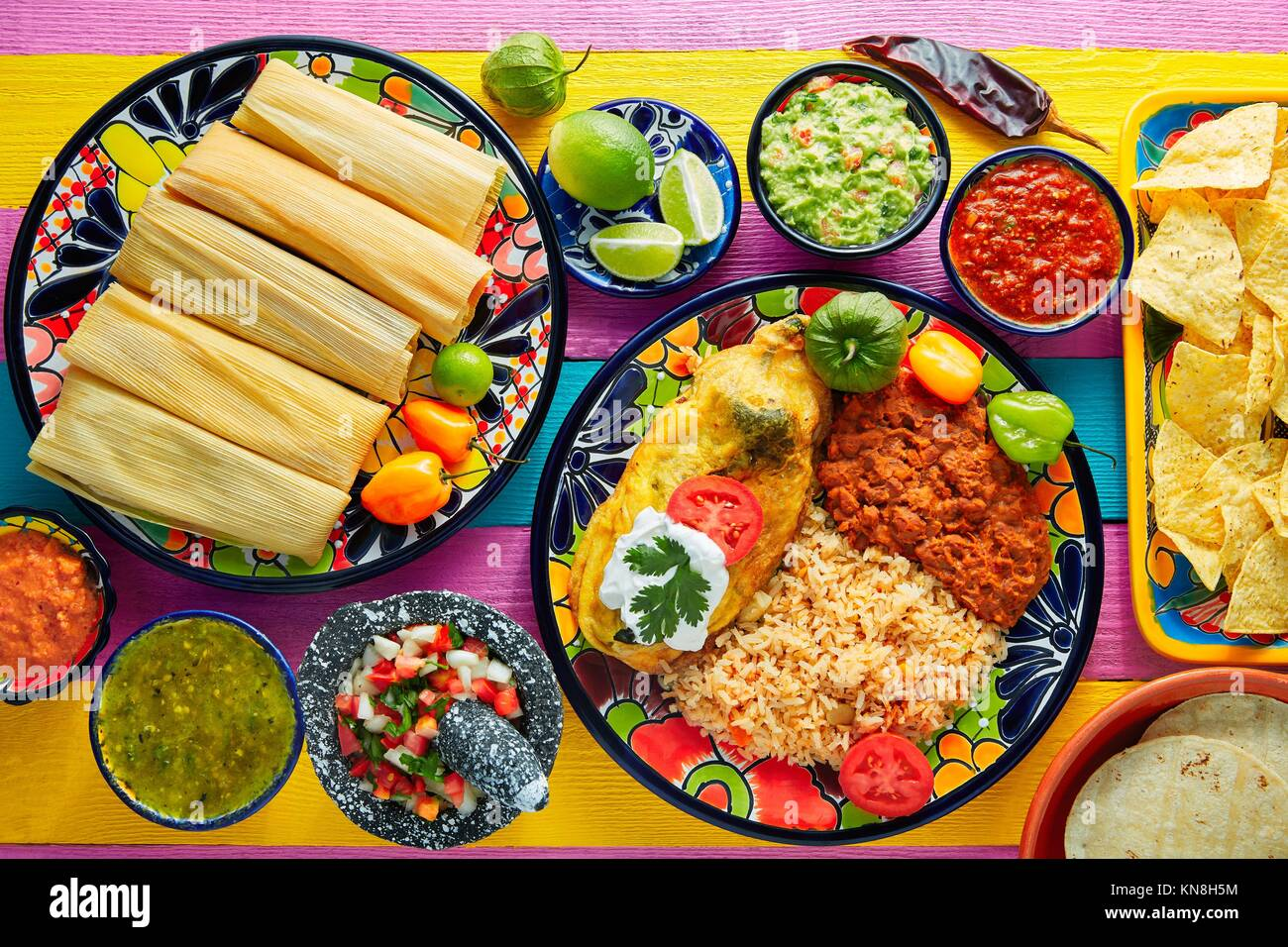 Tamale with corn leaf and filled chili pepper poblano guacamole sauces. - Stock Image