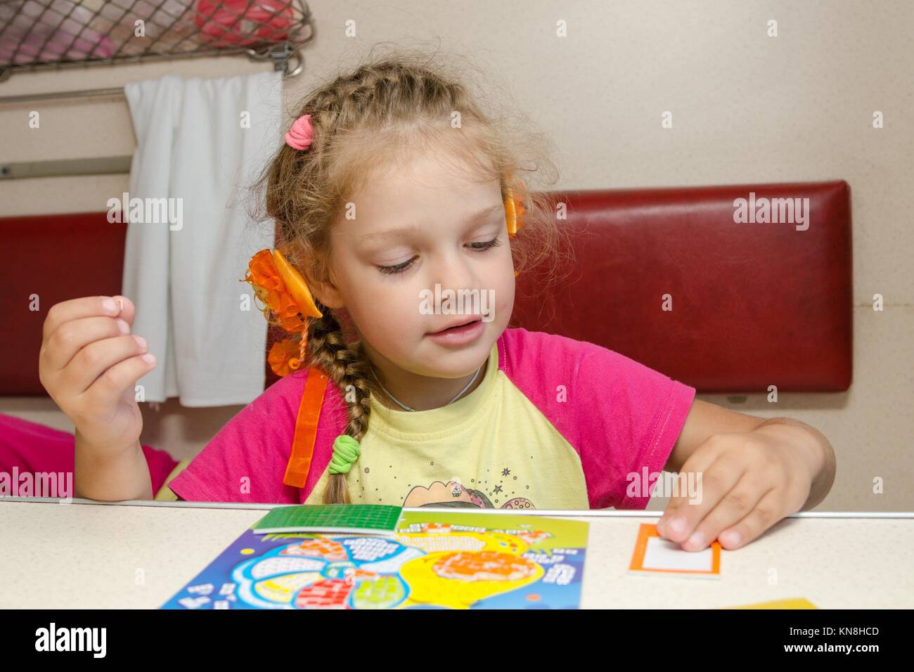 Little girl on the train sits at a table on the lower second-class place car and enthusiastically skin application. Stock Photo