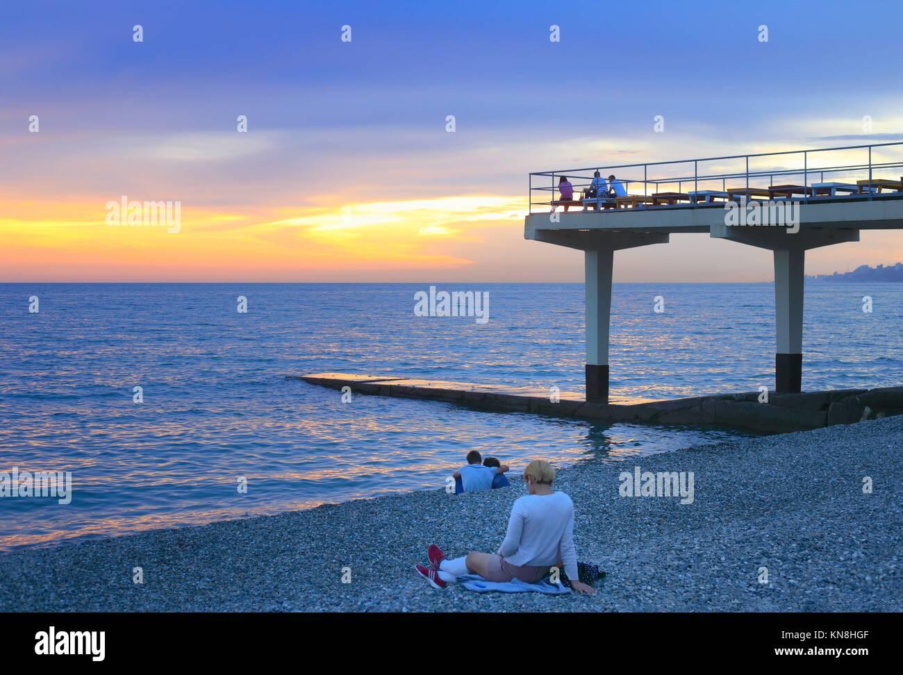 People sitting at Sochi seashore at evening. - Stock Image