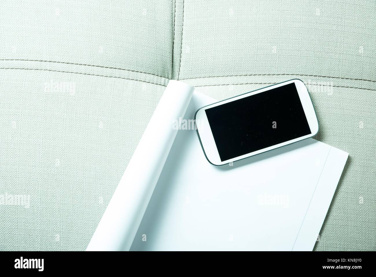 A smartphone and a exercise book lying on a sofa.. - Stock Image