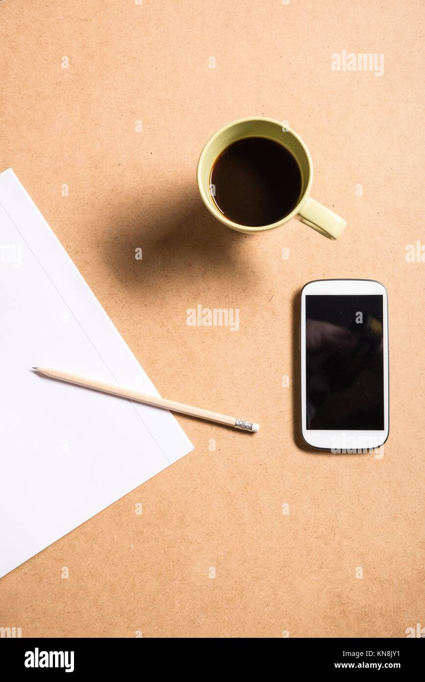 A smartphone and a exercise book on a wooden Desk.. - Stock Image