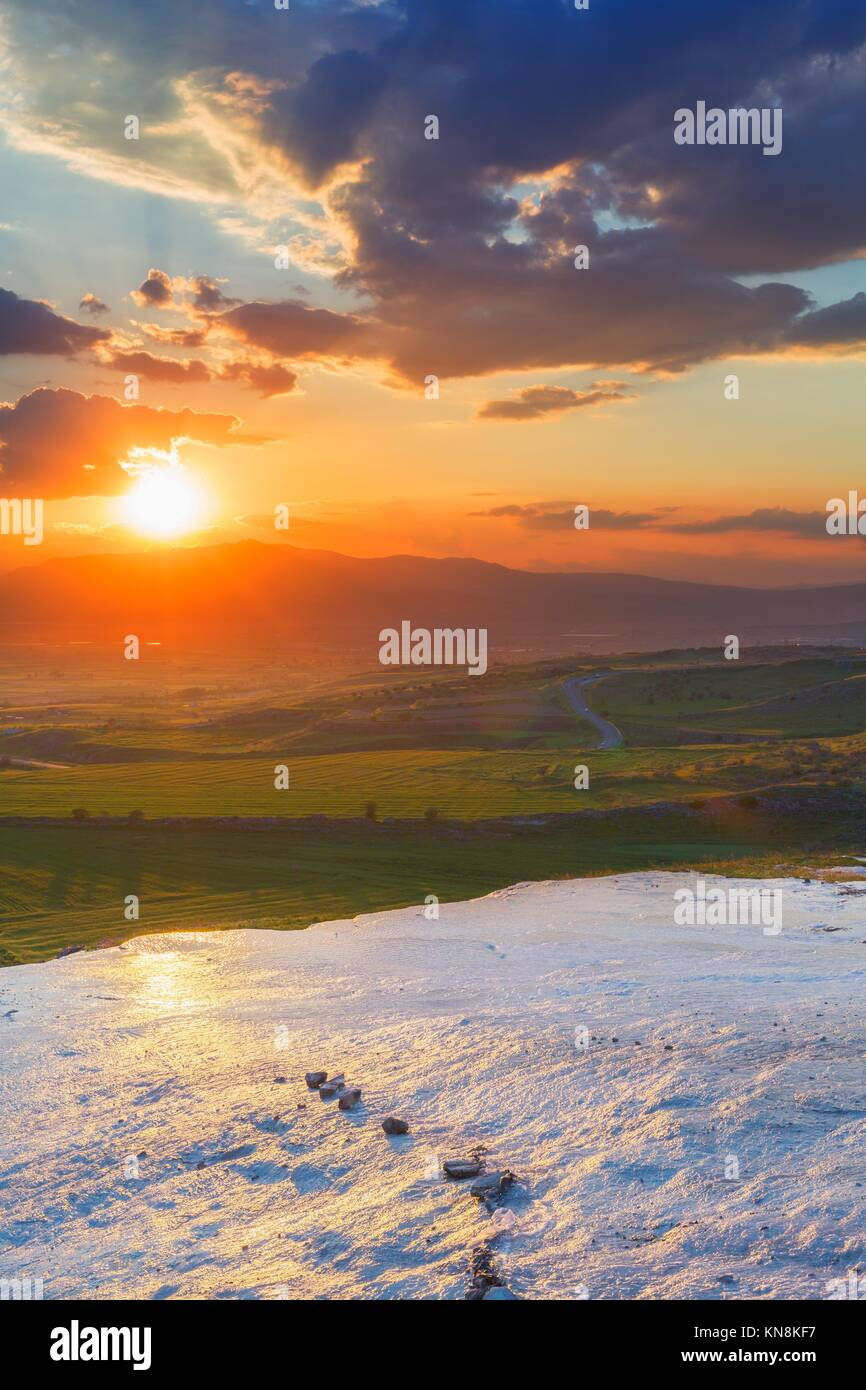 Sunset at the valley with glance surface on foreground. - Stock Image