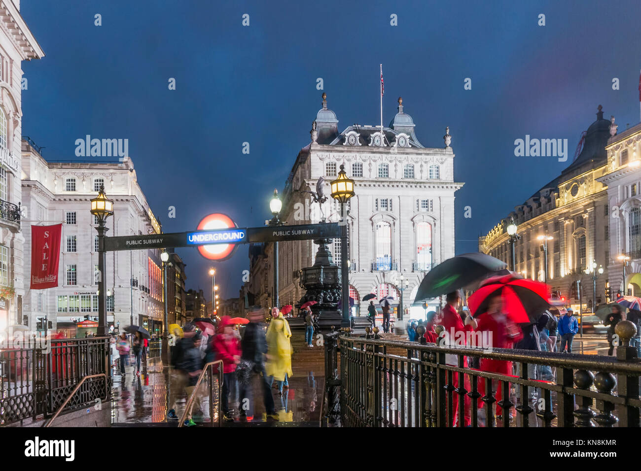 People with umbrellas, Piccadilly circus, rain, evening, Subway entrance, London, UK Stock Photo