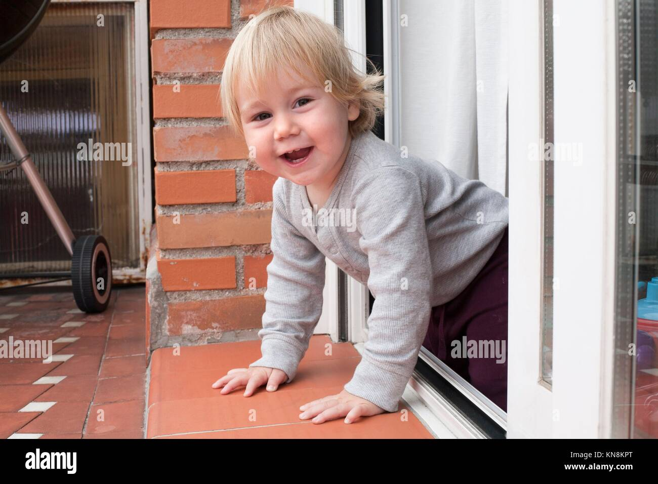 portrait of blonde caucasian baby nineteen month age chubby face looking at camera peering terrace floor supported Stock Photo