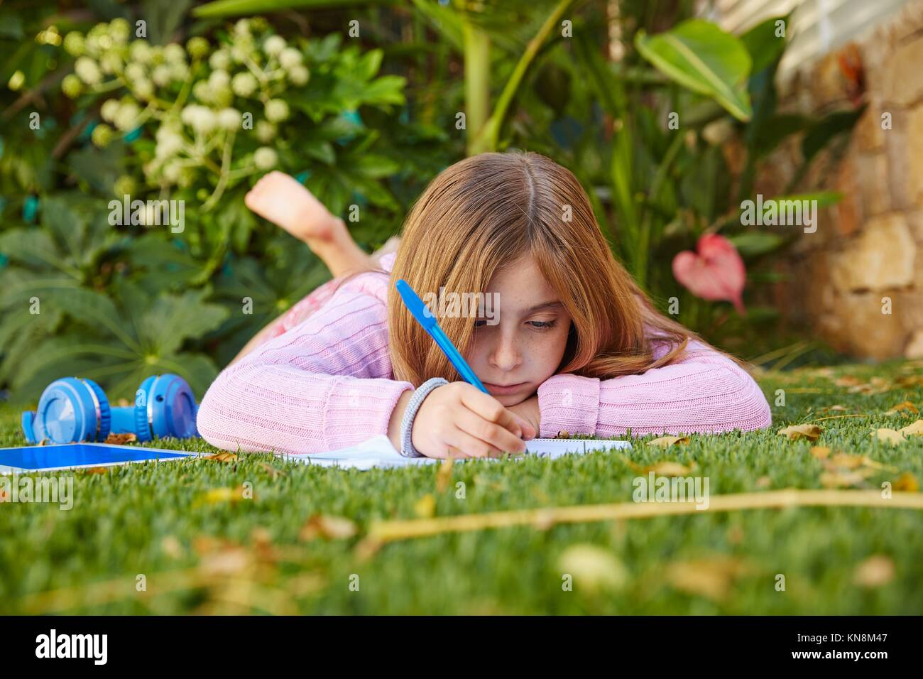 Blond kid girl homework lying on grass turf writting notebook. - Stock Image