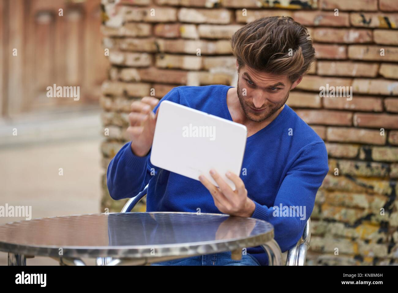Young man using tablet pc as a mirror to fix his hair in outdoor cafe. - Stock Image