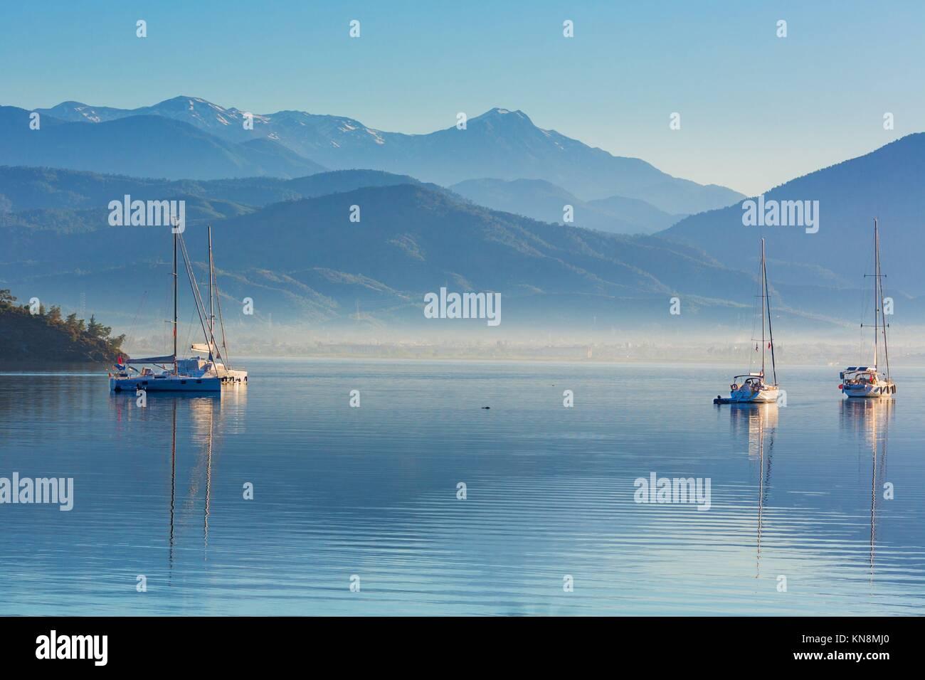 Anchored yachts at misty morning on the lake on mountains background, Fethiye, Mugla Province, Turkey Stock Photo