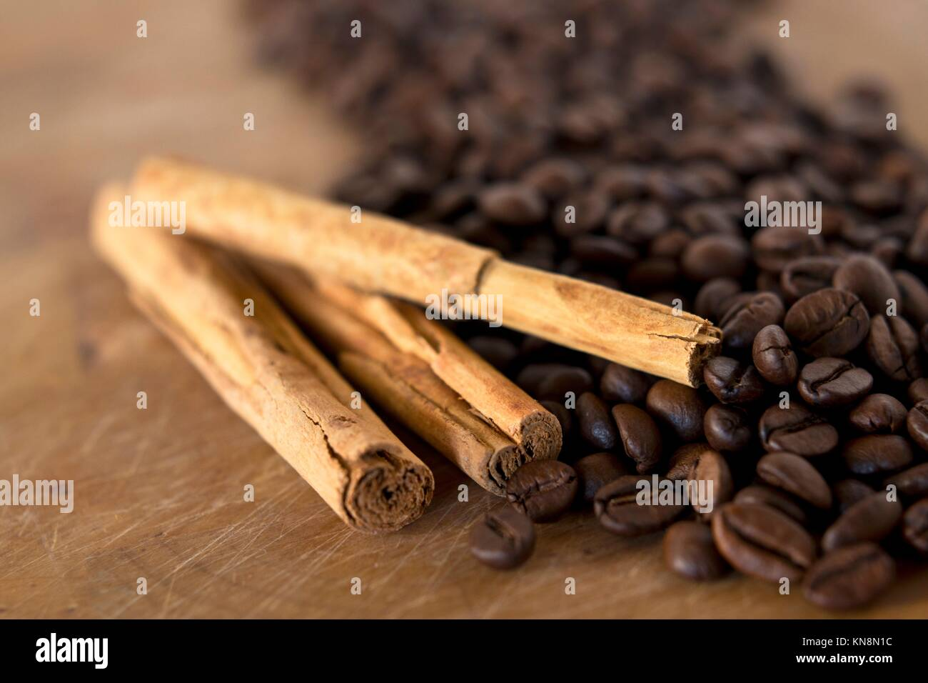 Detail of a pile of coffee beans and cinnamon background. Stock Photo
