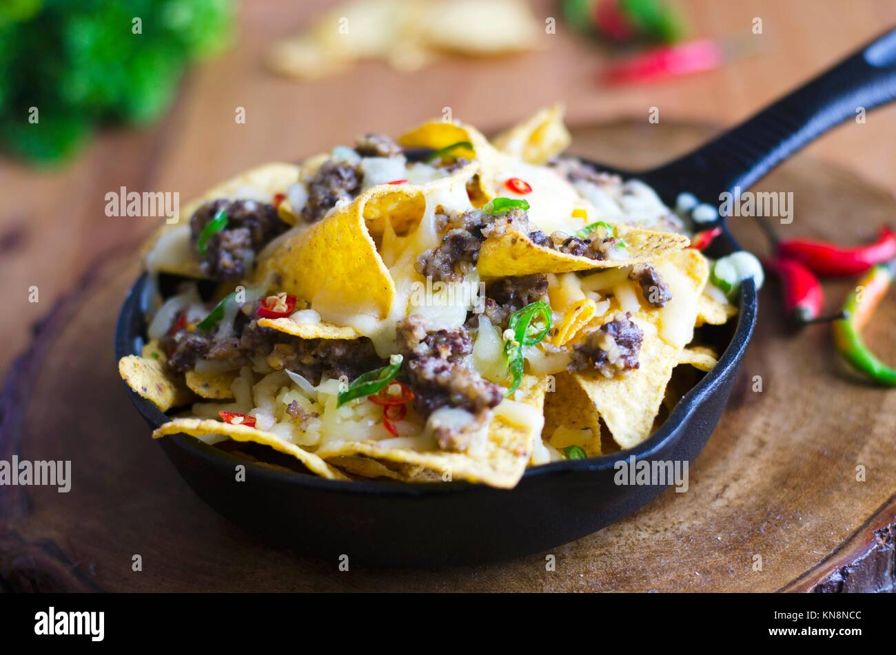 Nachos with haggis, melted cheese and chilli peppers. Stock Photo